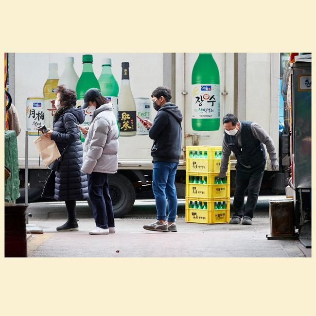 공적 마스크를 구매하려고 줄선 사람들 사이로 한 배달원이 시장으로 막걸리 상자를 나르고 있다.
