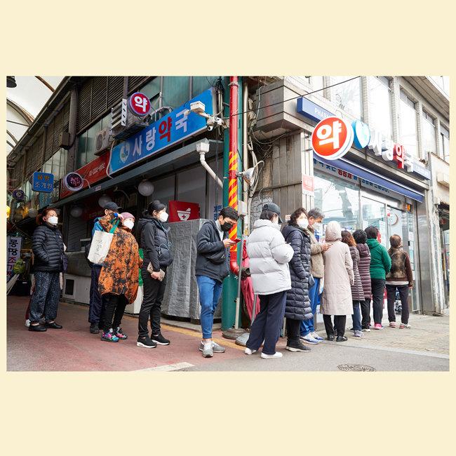 이른 아침부터 공적 마스크 구매를 위해 약국 앞에 모인 사람들.