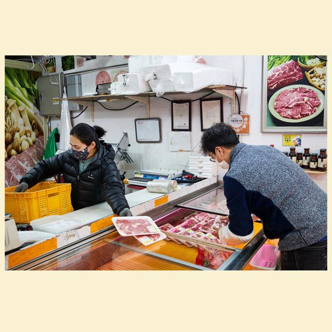 한 정육점 상인이 오늘 판매할 고기를 냉장 진열대에 넣고 있다.