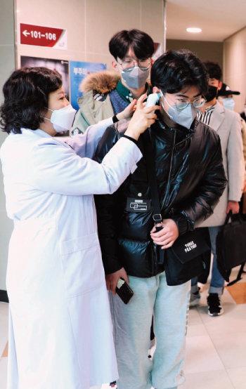 한국교통대는 3월 13일 기숙사에 머물던 중국인 유학생 전원을 격리 해제했다. 이날 기숙사를 나서는 중국인 유학생들이 발열 검사를 받고 있다. [뉴시스]