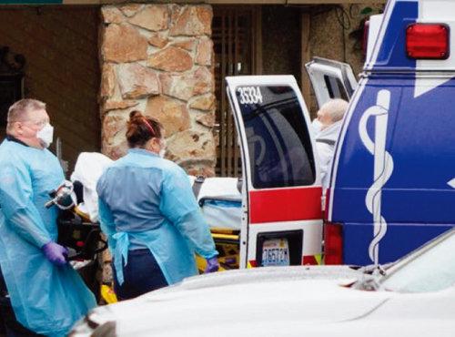 미국 뉴욕주 응급요원들이 코로나19 환자를 구급차에 타우고 있다. [USA 투데이]
