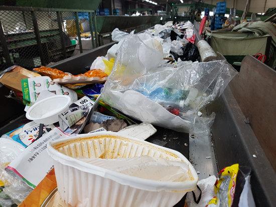 4월 14일 서울 송파구 송파자원순환공원 내 재활용쓰레기 분류 작업장 컨베이어 벨트 위에 배달음식 용기로 쓰인 폐플라스틱 등 쓰레기가 놓여 있다. [최진렬 기자]