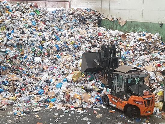 4월 14일 서울 송파구 송파자원순환공원에서 쓰레기선별업체 근로자가 재활용쓰레기 선별장에 쌓인 쓰레기를 처리하고 있다. [최진렬 기자]
