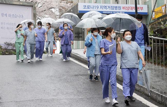 3월 27일 비가 내리는 가운데 대구 계명대 동산의료원 간호사들이 근무를 하기 위해 보호구 착의실로 향하고 있다. [뉴시스]