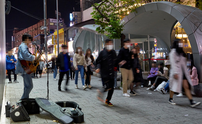 서울 홍대 '걷고 싶은 거리'에서 많은 행인이 지나가는 가운데 한 아티스트가 버스킹을 하고 있다.