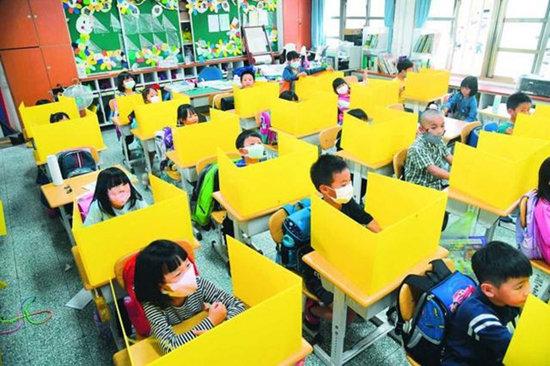 대만 초등학생들이 노란색 개인용 칸막이를 책상에 놓은 채 수업하고 있다. [CNA]