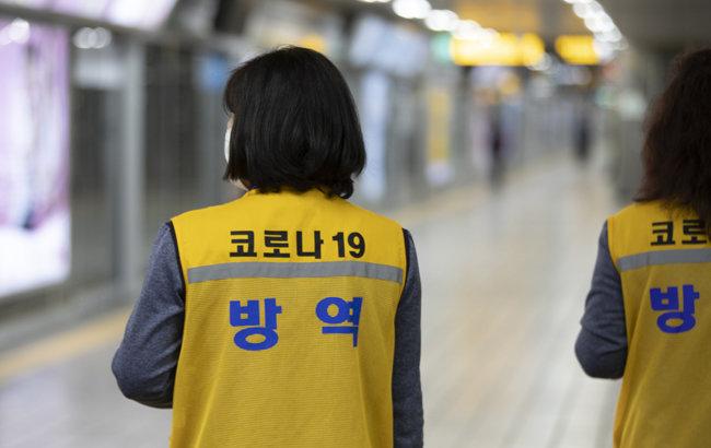 '코로나 방역'이라고 쓰인 조끼를 입고 있는 서울지하철 2호선 을지로입구역 지하철 미화원의 뒷모습. [지호영 기자]