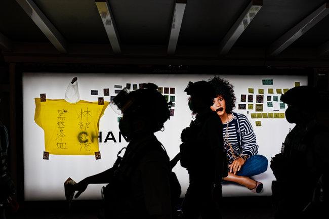 경찰이 2020년 5월 15일 중국 홍콩에서 논란이 된 범죄인 인도법안에 반대하는 시위 도중 지난해 사망한 시위자를 추모하는 밤샘 시위 도중 민주화 시위 포스트잇과 함께 놓여진 노란 우비를 지나가고 있다. [GETTYIMAGES]
