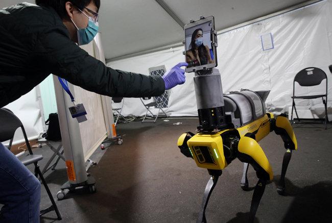 과학자 헨웨이 황(왼쪽)이 2020년 4월 22일 보스턴 브리검 앤 여성 병원에서 열린 시연에서 로봇에 대해 설명을 하고 있다.