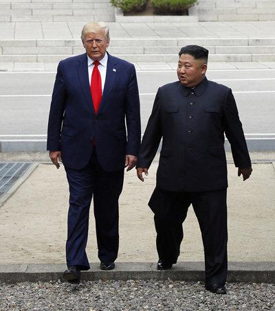 2019년 6월 30일 도널드 트럼프 미국 대통령과 김정은 북한 국무위원장이 판문점 군사분계선 북측 지역에서 만나 인사한 뒤 남측 지역을 향해 이동하고 있다. [뉴시스]