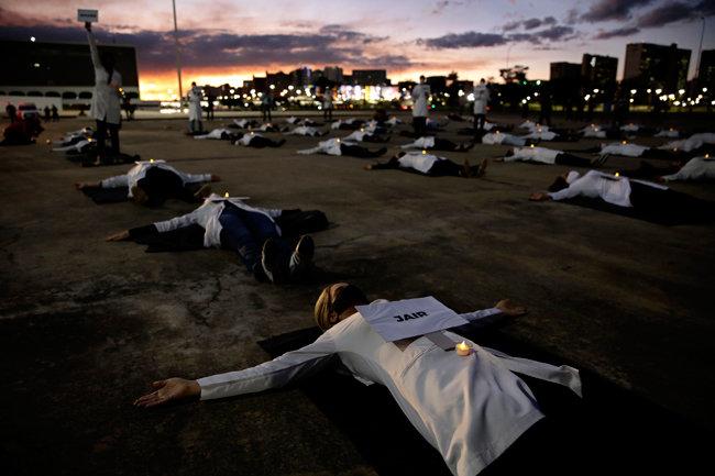 브라질에서 간호사들이 신종 코로나바이러스 감염증(코로나19)에 맞서 일선에서 근무 중 숨진 동료의 이름이 적힌 종이와 추모 촛불을 배에 올려놓고 바닥에 누워 시위하고 있다. [AP/뉴시스]