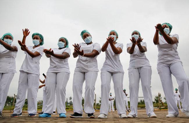 케냐  케냐타 대학 주차장에서 신종 코로나바이러스 감염증(코로나19) 환자들을 돌보는 간호사들이 스트레스와 업무의 어려움을 해소하는 데 도움을 주는 줌바 댄스 수업에 참여하고 있다. [AP/뉴시스]