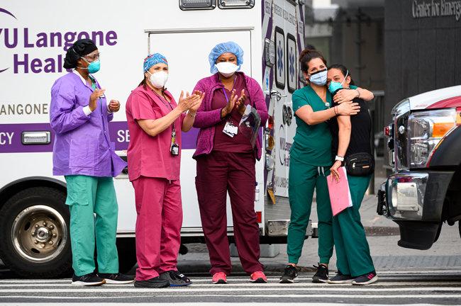 뉴욕에서 코로나바이러스 유행 당시 의료진과 필수 노동자들에게 감사를 표하기 위해 박수갈채를 보내는 동안 의료 종사자들이 뉴욕 주립 랑곤 병원 밖에 서 있다. [Getty Images]