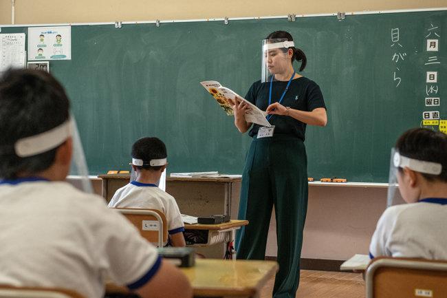 .플라스틱 페이스 바이저를 착용한 교사가 기누가와 초등학교에서 수업을 하고 있다.