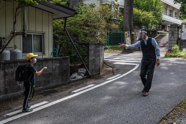 일본 닛코, 기누가와 초등학교 교장 다케다 사이오(오른쪽)가 2020년 6월 3일 일본 닛코에서 학교에 도착한 제자와 함께 가위바위보를 할 때 플라스틱 페이스 바이저를 착용하고 있다.