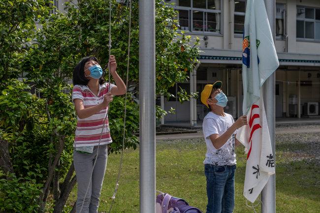 얼굴 마스크를 쓴 아이들이 국기와 교기를 게양한다.