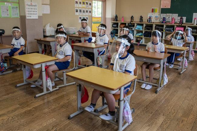 .플라스틱 페이스 바이저를 착용한 어린이들이 교실에 앉아 있다.