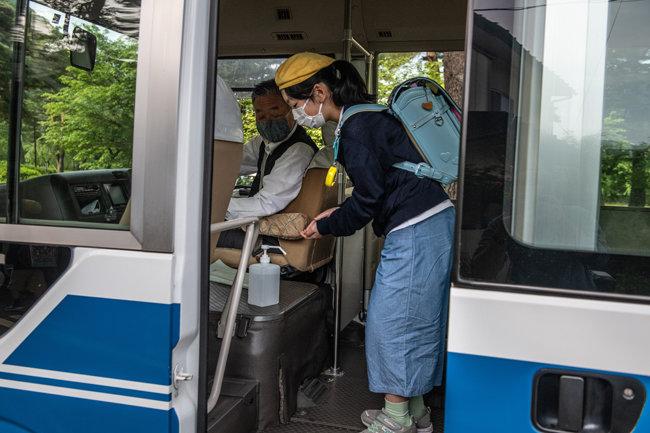 통학버스에서 내리기 전에 손 세정제를 사용한다.
