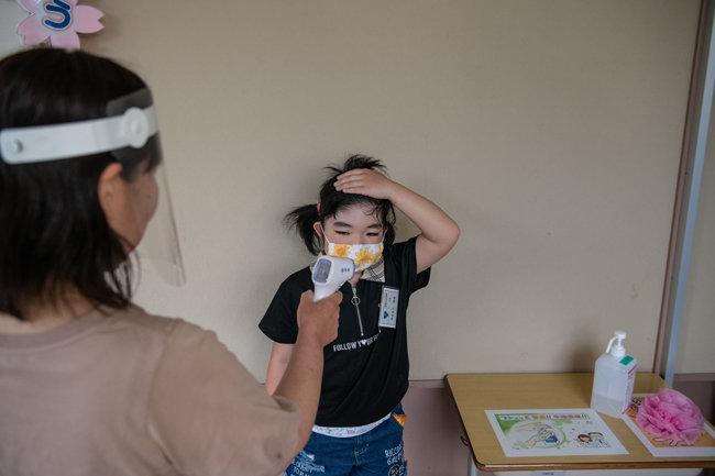 학교 간호사가 체온을 재고 있다.
