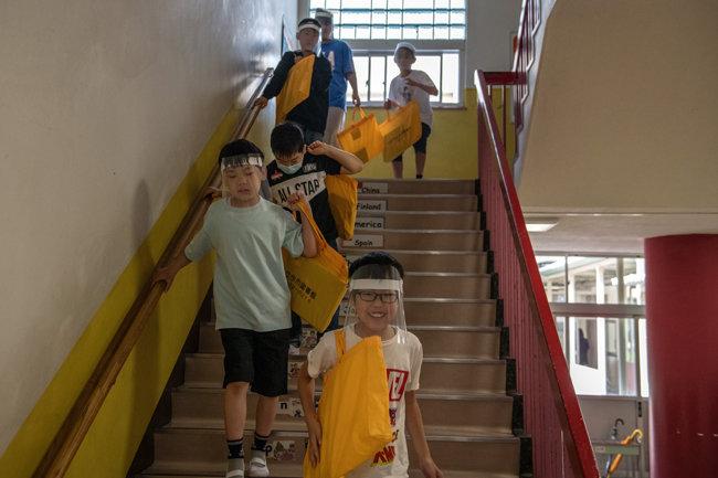 플라스틱 바이저를 착용한 어린이들이 교실로 걸어가고 있다.