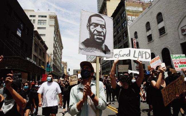 6월 2일(현지) 미국 캘리포니아주 로스앤젤레스에서 시위대가 경찰관에게 살해된 조지 플로이드의 대형사진을 들고 행진하고 있다. [뉴시스]