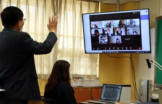 5월 14일 경기 성남시 운중중 학생들이 쌍방향 온라인 수업을 시작하기 전 선생님에게 인사하고 있다. [동아DB]