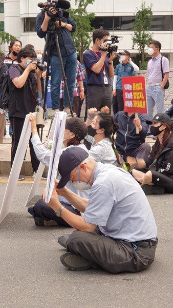 한 노인이 부동산 촛불집회 현장에서 바닥에 앉은 채 휴식을 취하고 있다. [박해윤 기자]