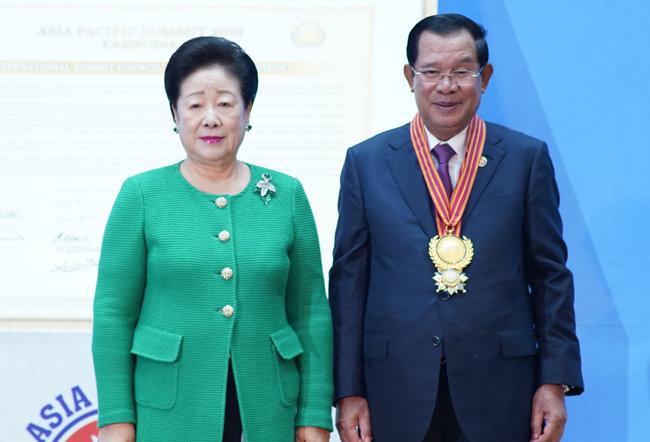 2019년 11월 한학자 가정연합 총재가 캄보디아 프놈펜 캄보디아 총리 집무실 평화궁에서 훈센 캄보디아 총리에게 굿 거버넌스 상을 수여하고 있다. [가정연합 제공]