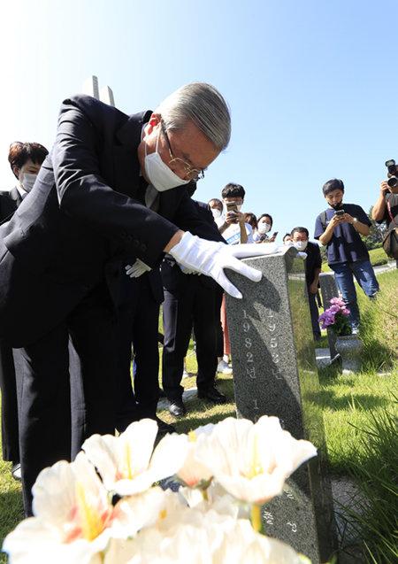 김 위원장이 5·18 민주묘지에서 박관현 열사 묘비를 어루만지며 참배하고 있다.