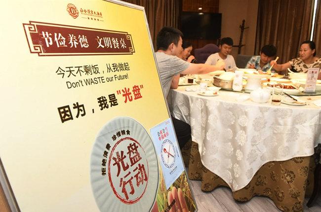 중국의 한 식당에서 손님들이 잔반줄이기 표지판 옆에서 식사하고 있다. [CNA]