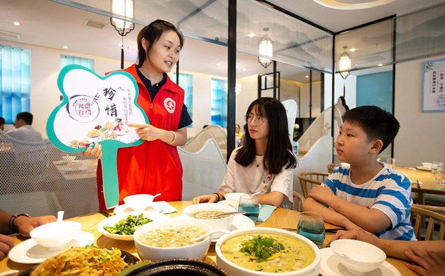 중국의 한 식당에서 종업원이 손님들에게 잔반 줄이기 운동을 설명하고 있다. [VCG]