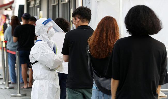 시민들이 코로나19 검사를 받기 위해 선별진료소 앞에 줄 서 있다. [뉴시스]