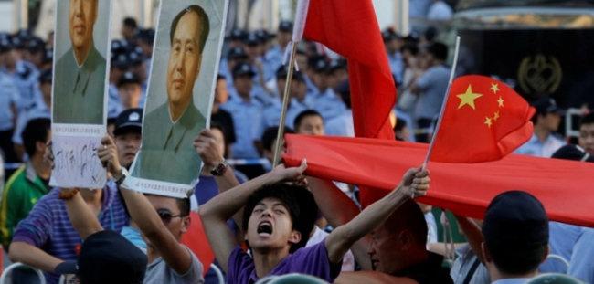 중국 젊은이들이 마오쩌둥 전 주석사진과 오성홍기를 들고 시위하고 있다. [AP]