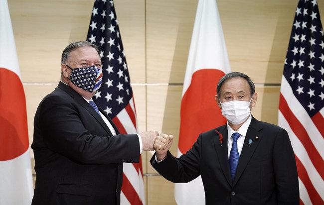 스가 요시히데 일본 총리(오른쪽)와 마이크 폼페이오 미국 국무장관이 10월 6일 일본 도쿄에서 만나 주먹 인사를 하고 있다. [도쿄=AP 뉴시스]