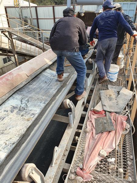 10월 31일현장 노동자들이 안전장비 없이 고층에 위치한 컨베이어벨트로 올라가 해진 부분을 깁고 있다. [최진렬 기자]