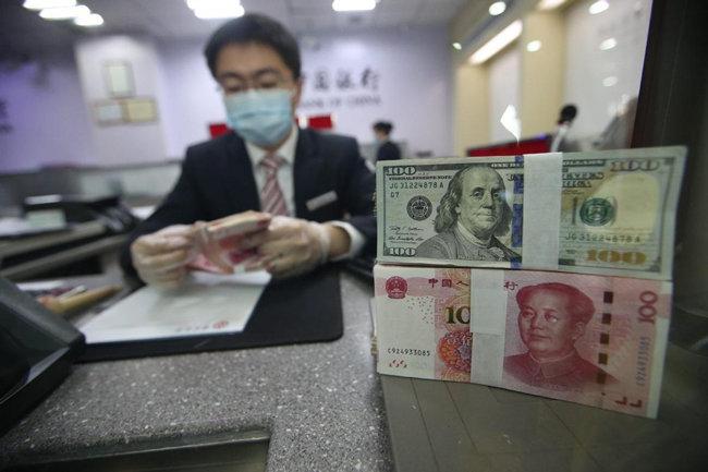 중국 은행원이 위안화를 달러화로 교환해주고 있다. [China Daily]