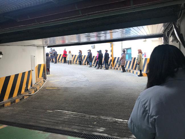 12월 12일 오전 10시, 서울 구로보건소 선별진료소에 코로나검사 번호표를 받기 위해 줄 서 있는 대기자들. 이 줄은 보건소주차장 입구에서 시작해 건물 지하 2층까지 길게 이어져있다. [한여진 기자]