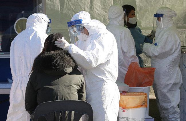 15일 서울역 광장에 설치된 임시 선별진료소에서 의료진이 신종 코로나바이러스 감염증 검사를 진행하고 있다. [뉴스1]