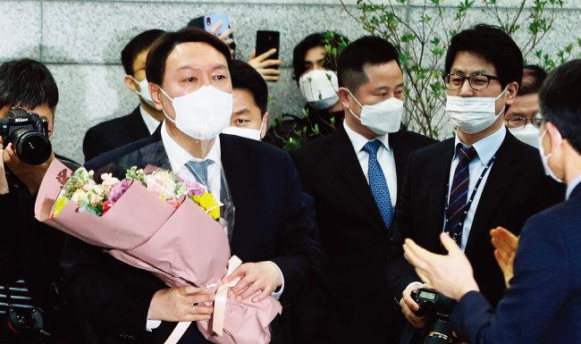 임기를 4개월여 남기고 물러나는 윤석열 검찰총장이 3월 4일 오후 직원들에게 인사한 뒤 꽃다발을 들고 대검찰청을 나서고 있다. [뉴스1]