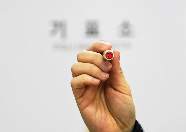 서울시장 보궐선거 전날인 4월 6일 서울 중구 장충동주민센터에 마련된 투표소에서 선거관리위원회 관계자가 투표 도장을 확인하고 있다. [뉴스1]