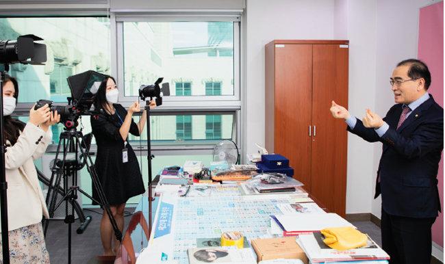 태영호 의원(오른쪽)이 4월 28일 의원실에 마련된 간이 스튜디오에서 보좌진의 요구에 맞춰 카메라를 향해 손가락 하트를 하고 있다. [조영철 기자]