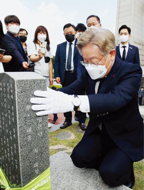 이재명 경기도지사가 5월 18일 광주 북구 국립5 ·18민주묘지를 찾아 5 ·18 최초 희생자인 김경철 열사의 묘비를 어루만지고 있다. [뉴스1]
