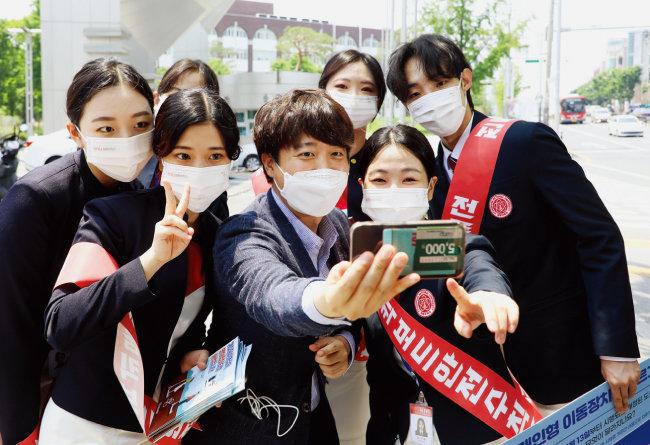 국민의힘 이준석 전 최고위원(가운데)이 5월 24일 대구 북구 경북대 북문 앞에서 대학생들과 기념사진을 찍고 있다. [뉴스1]
