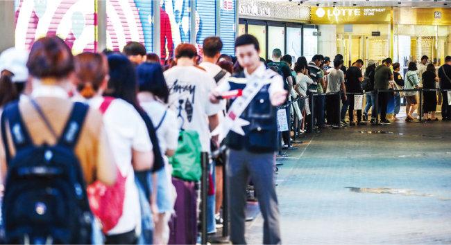 서울 중구 롯데면세점 본점 입구에서 중국인 관광객들이 면세점 개점을 기다리며 길게 줄 서 있다. [뉴스1]