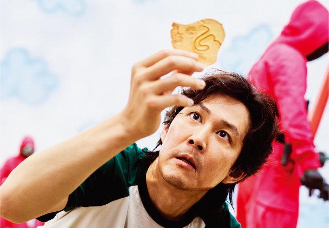 '오징어 게임'에서 주인공 기훈(이정재 분)이 우산 모양이 찍힌 달고나 뒷면을 쳐다보는 장면. [사진 제공 · 넷플릭스]