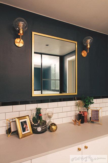 딥 블루 컬러 벽과 세련된 사이드 조명, 거울 등으로 스타일리시하게 연출한 파우더룸.