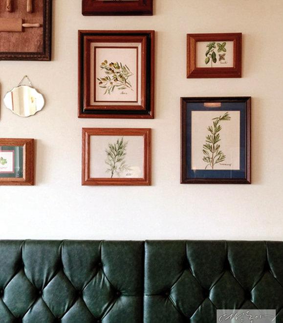 무심하게 지나칠 수 있는 소파 뒤 벽면은 나뭇잎으로 만든 액자를 리드미컬하게 세팅해 감각적인 공간으로 완성했다.