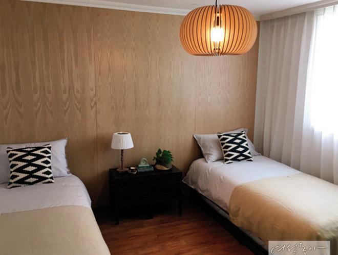 한쪽 벽에 나무 패널을 붙이고 트윈 침대를 두어 미니멀하게 꾸민 침실. 유니크한 디자인의 조명과 쿠션으로 포인트를 줬다.