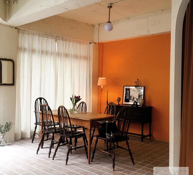 벽 한 면을 톤 다운된 오렌지 컬러로 페인트칠해 경쾌한 분위기를 더한 카페. 화이트 인테리어가 싫증날 때 시도하기 좋은 아이디어다.