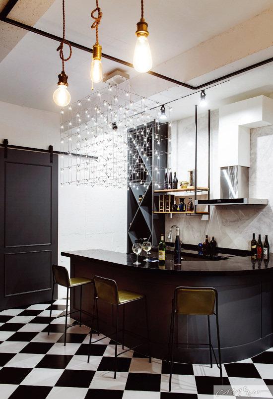 1층 와인 바. 바닥에 블랙 & 화이트 타일을 깐 뒤 그레이 바 테이블과 수납장을 설치해 감각적인 공간을 완성했다. 작은 전구를 와이어로 이어 만든 커다란 샹들리에로 포인트를 준 뒤 골드 조명으로 빈티지한 느낌을 더했다.